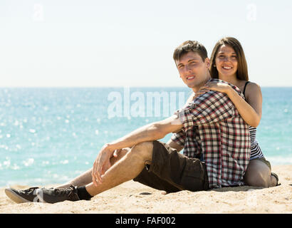 Young smiling couple sitting on the sea sand summer day - Stock Photo
