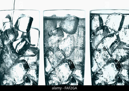 Photographic composite showing three stages of soda being poured over ice in a glass tumbler. - Stock Photo