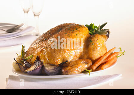 Freshly oven roasted chicken served with roast vegetables on a platter and ready for carving. - Stock Photo