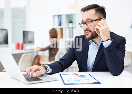 Confident businessman typing on laptop and speaking on the phone - Stock Photo