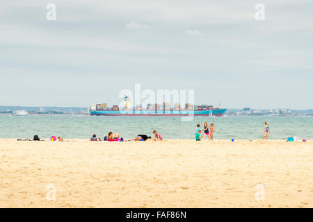 People sunbathing on the beach at Ryde Isle of Wight UK with a large container ship going past in the sea - Stock Photo