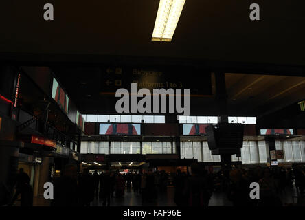 Interior view, towards entrance doors, silhouettes of people, east side of Main Concourse, Euston Station, London, - Stock Photo