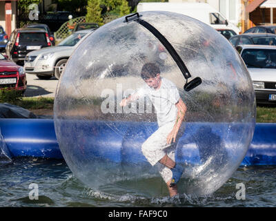 Boy standing up running in an inflatable ball bubble zorbing on a pool of water. Polanica-Zdroj, Klodzko, Poland, - Stock Photo