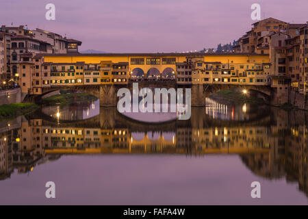 Ponte Vecchio over the Arno with symmetrical reflection in water, dusk, Florence, Tuscany, Italy - Stock Photo