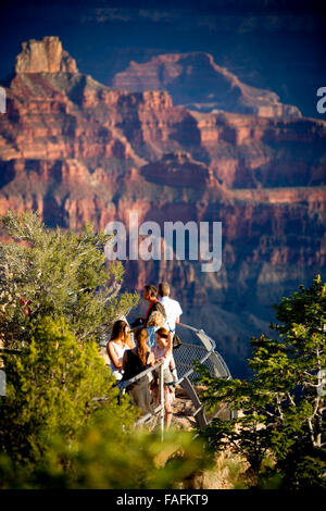 people looking at the view of the grand canyon from a lookout at sunrise. - Stock Photo