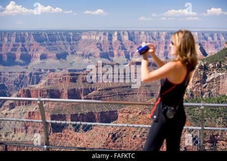 Woman taking photographs of the Grand Canyon. Arizona. USA - Stock Photo