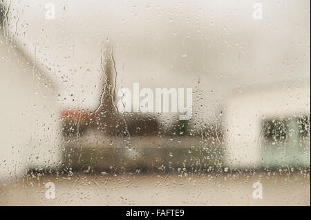 church and spire of church against skyline looking out from very wet rainy window with drops droplets running down - Stock Photo