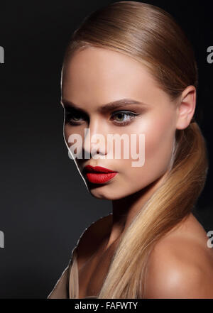 Young woman with straight hair and and red lips on dark background. Portrait. - Stock Photo