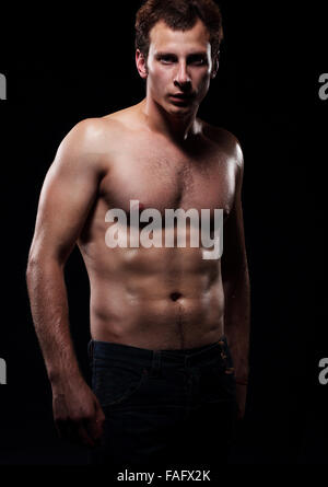 The beautiful and strong young  guy.  Photoshoot in a studio, dark background. - Stock Photo