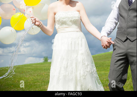 A young bride & groom holding hands on their wedding day - Stock Photo