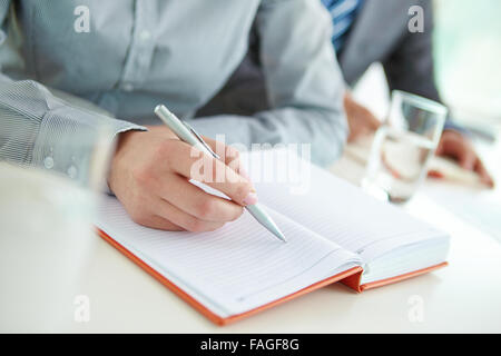 Female hand with pen on empty page of notebook - Stock Photo