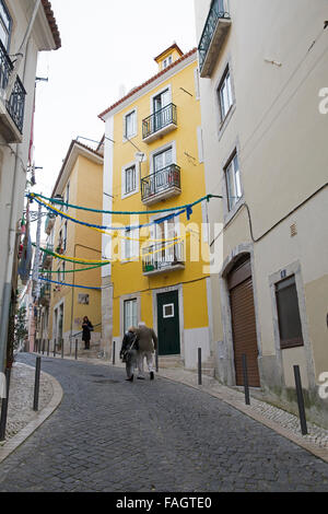 People walk through the Narrow street with yellow buildings in Lisbon Portugal - Stock Photo
