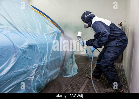 Vehicle varnisher in the paint spraying cabin. - Stock Photo