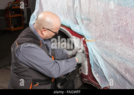 Car-body firm works on a wing with an angle grinder. - Stock Photo