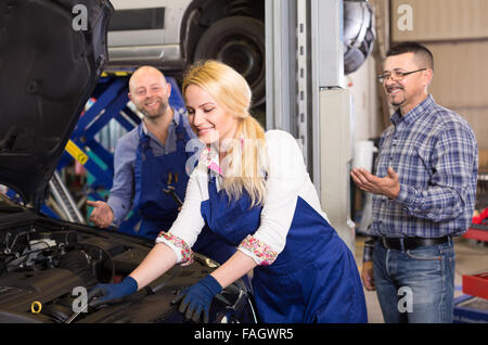 Female mechanic is fixing something under the hood of a car with a wrench while her colleague and owner are standing - Stock Photo