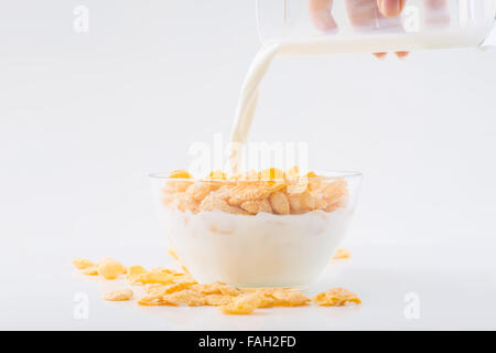 Glass of milk is being poured into cornflakes bowl. - Stock Photo