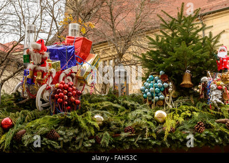 gift boxes, glass balls and a Santa puppet between spruce branches on roof of Christmas market stall,  Stuttgart, - Stock Photo