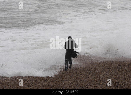 Dorset, UK. 30th Dec, 2015. Taking snaps and taking risk as this wave watcher was caught by the sea at Chesil Cove, - Stock Photo