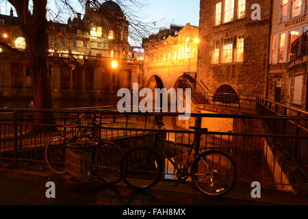 Pulteney Bridge,River Avon, Bath, At night seen from below with two bikes next too railings. - Stock Photo