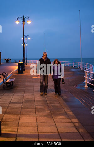 Aberystwyth, Wales, UK. 30th Dec, 2015. UK Weather:  A couple walk hand in hand on the Prom at sundown making good - Stock Photo
