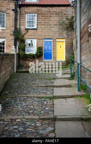 Cobbled path leading to a terraced house in the lower bay area of Robin Hoods Bay in North Yorkshire UK - Stock Photo
