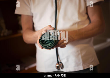 Doctor holding a blood pressure cuff and wearing a stethoscope - Stock Photo