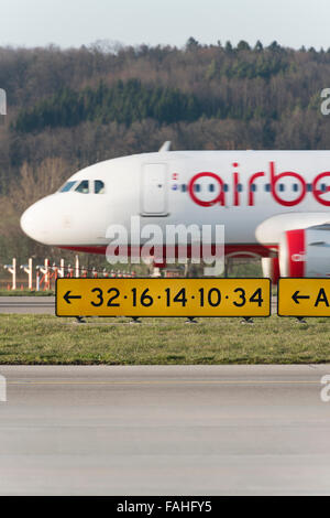 During takeoff from Zurich airport, an Airbus of German airline Air Berlin is passing behind the runway signalisation. - Stock Photo