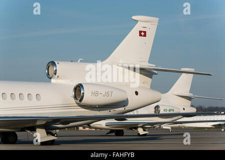 Two Dassault Falcon 7X executive jets parked in the warm evening light at Zurich international airport - Stock Photo