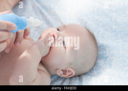 Mother using baby nasal aspirator. She is doing a mucus suction to three months baby boy - Stock Photo
