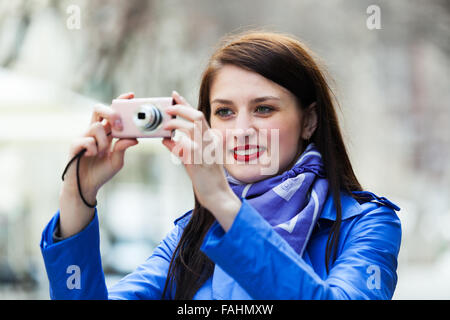 Happy girl with digital camera taking a photo at street - Stock Photo