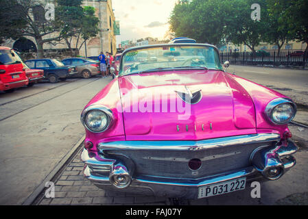 HAVANA, CUBA - 4 DEC, 2015. Pink vintage classic American car, commonly used as private taxi parked in Havana street. - Stock Photo