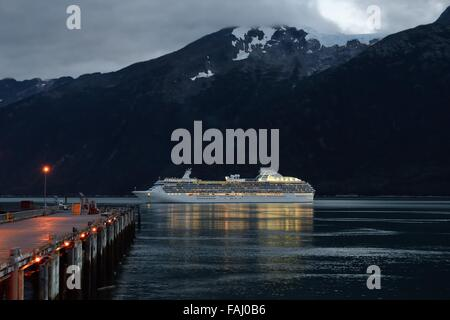 The Coral Princess cruise ship leaving Skagway harbour on a late evening sailing in Alaska, USA. - Stock Photo