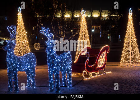 Brightly lit raindeers and sleigh. Christmas city decoration. - Stock Photo
