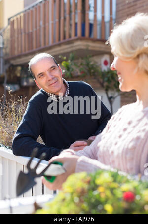 Positive elderly woman with horticultural sundry and aged man drinking tea in patio - Stock Photo