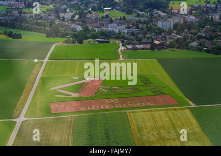 Aerial image of a super-size Victorinox Swiss army knife advertisement in a crop field. - Stock Photo