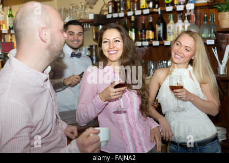 Cheerful young adults waiting for table and having beverages at tavern. Focus on girl - Stock Photo