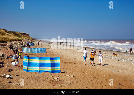 Families enjoy a September day behind wind-breaks on Mappleton Beach with a sea breeze on an sunny day. Copy space - Stock Photo