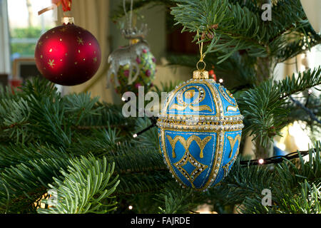Christmas decorations on a Spruce Christmas Tree. Blue and gold bejeweled egg with other baubles. - Stock Photo