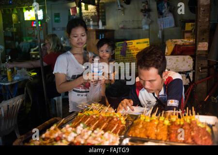Family Street food vendors in Khao San Road, Bangkok, Thailand. Khaosan Road or Khao San Road is a short street - Stock Photo