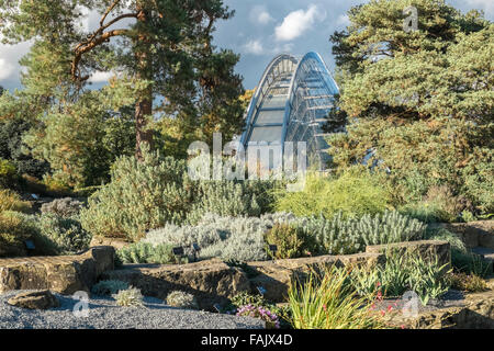 Alpine glass house building viewed through the rock garden, Royal Botanic Gardens, Kew, London, England UK - Stock Photo