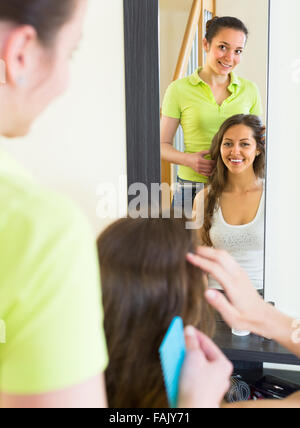 Cheerful smiling young woman brushing her friend in front of the mirror at home - Stock Photo