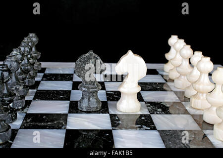 White Knight vs. Black Knight on a marble chess board - Stock Photo