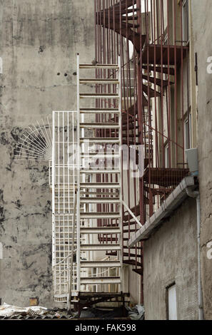 System of metal staircase, of colors white and chrome, on the outside of an abandoned building - Stock Photo