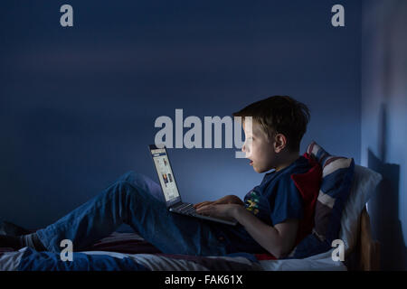 A boy sitting up late in his bedroom looking at the internet shocked at what he is seeing - Stock Photo