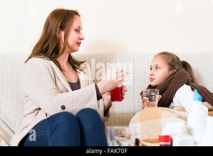 A mother and her sick daughter are on a sofa indoors. Woman gives her ill child cough syrop - Stock Photo