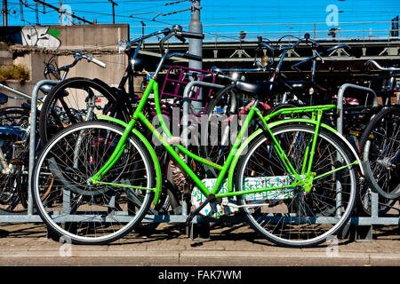 Green bike parked near the railway. Amsterdam, Holland, Netherlands, Europe. Climate change, global warming. Eco - Stock Photo