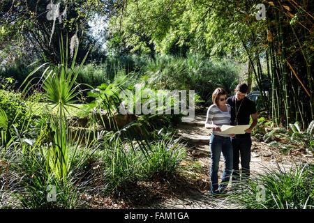 Gainesville Florida Kanapaha Botanical Gardens plants trees nature man woman couple looking map trail - Stock Photo