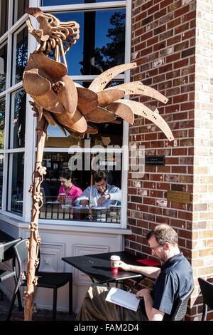 Gainesville Florida SE 1st Street Starbucks Coffee cafe alfresco man woman couple art metal sculpture rooster - Stock Photo