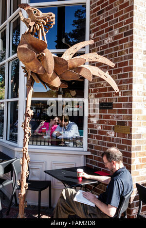 Gainesville Florida SE 1st Street Starbucks Coffee cafe alfresco man woman couple romantic art metal sculpture rooster - Stock Photo