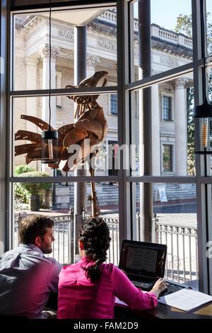 Gainesville Florida SE 1st Street Starbucks Coffee cafe inside man woman couple art metal sculpture rooster Hippodrome - Stock Photo